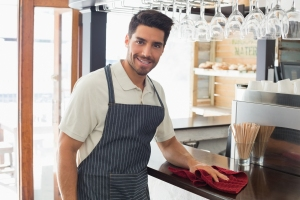 Portrait of a young smiling waiter cleaning countertop with spon